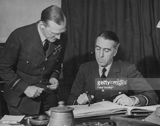 Air Marshal Sir Richard Peirse Commander in Chief of Bomber Command going through a book of records with his senior administrative officer December...