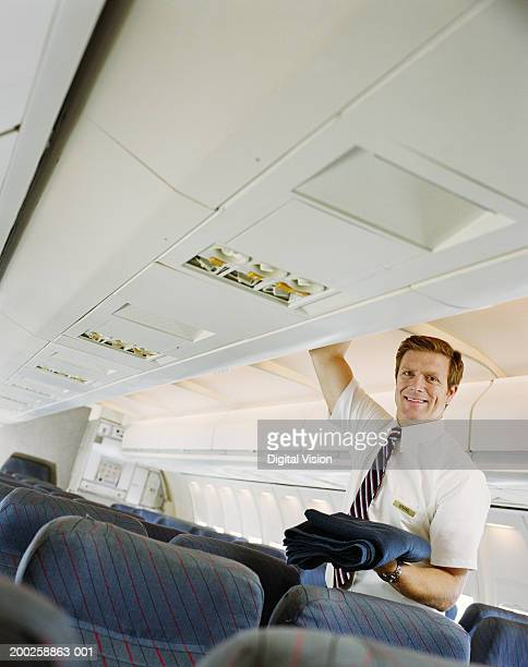Air steward holding blanket from overhead locker on plane, smiling