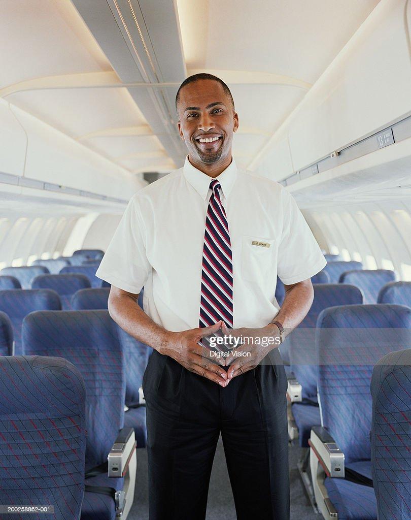 Air steward standing in aisle of aeroplane, smiling, portrait