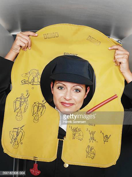 Air stewardess demonstrating with deflated life jacket, portrait