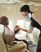 Air stewardess handing drink to male passenger, smiling