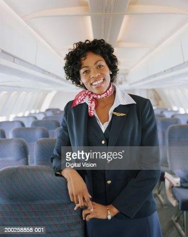 Air stewardess on aeroplane, smiling, portrait