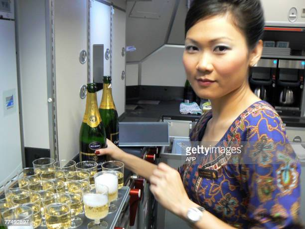 Air stewardess prepares champagne for passengers on board the A380's first commercial flight during the journey on the first Singapore Airlines...