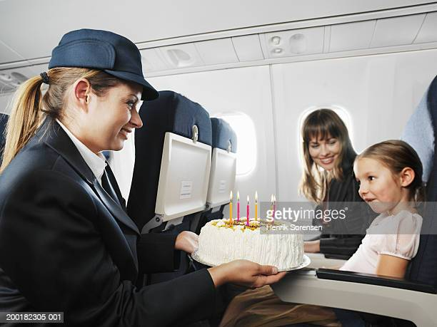Air stewardess presenting birthday cake to seated girl (5-7)