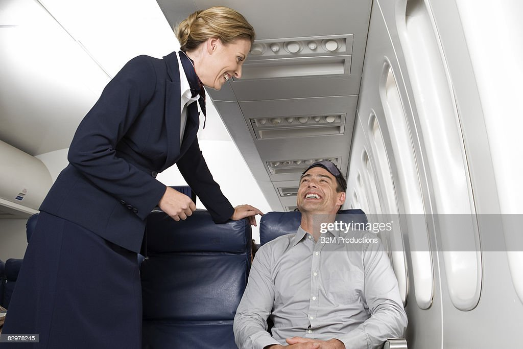 Air stewardess speaking to male passenger, smiling : Stock Photo