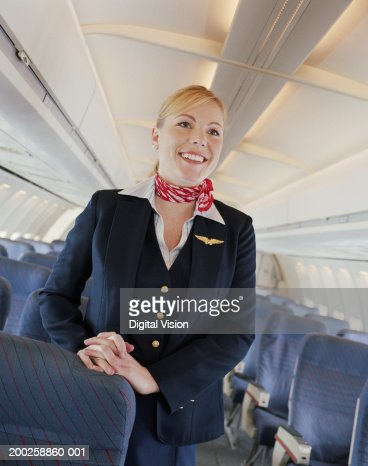 Air stewardess standing in aisle of aeroplane, smiling