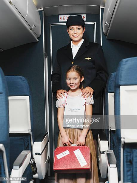 Air stewardess standing in aisle with girl (5-7), portrait