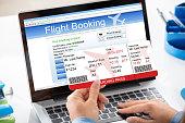 A Woman Booking Flight Online Using Laptop