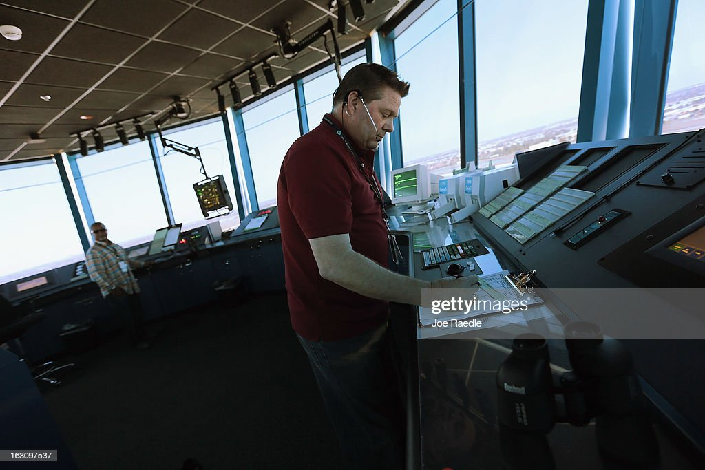 Air Traffic Controller, David Spitnale, (R) and Robert Moreland work in the control tower at Opa-locka airport on March 4, 2013 in Opa-locka, Florida. Due to sequestration cuts, small airports such as Opa-locka, which is a popular spot for corporate jets to land, will close its control tower in April to save federal transportation dollars under the federal spending cuts that went in to affect last week. Even though the control tower will close, planes will still be able to use the airport just without the help from the control tower.