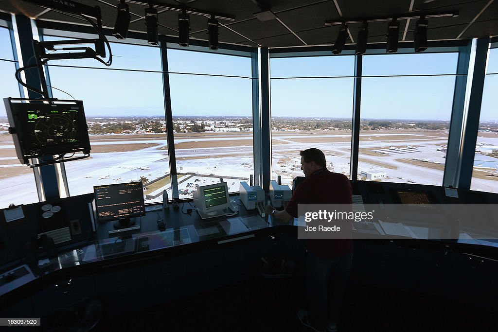 Air Traffic Controller, David Spitnale, works in the control tower at Opa-locka airport on March 4, 2013 in Opa-locka, Florida. Due to sequestration cuts, small airports such as Opa-locka, which is a popular spot for corporate jets to land, will close its control tower in April to save federal transportation dollars under the federal spending cuts that went in to affect last week. Even though the control tower will close, planes will still be able to use the airport just without the help from the control tower.