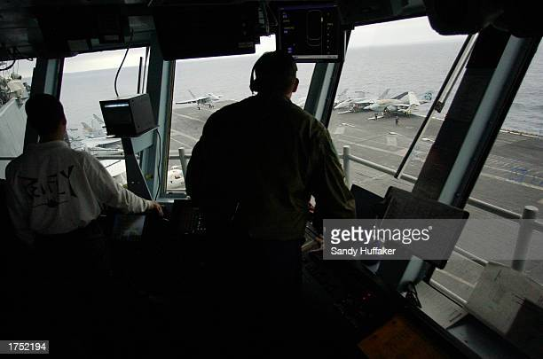 Air traffic controllers help an FA/18 Hornet land on the flight deck of the USS Nimitz January 29 2003 off the coast of Southern California The...