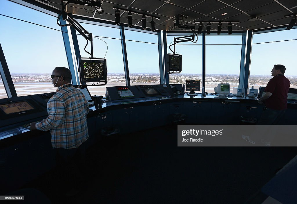 Air Traffic Controllers Robert Moreland (L) and David Spitnale work in the control tower at Opa-locka airport on March 4, 2013 in Opa-locka, Florida. Due to sequestration cuts, small airports such as Opa-locka, which is a popular spot for corporate jets to land, will close its control tower in April to save federal transportation dollars under the federal spending cuts that went in to affect last week. Even though the control tower will close, planes will still be able to use the airport just without the help from the control tower.