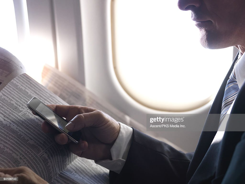 Air traveler sends text, with financial columns, : Stock Photo