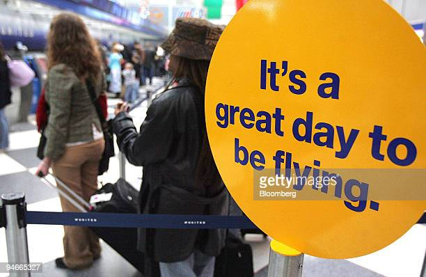 Air travelers wait to checkin for flights near a sign that reads 'It's a great day to be flying' in Terminal 1 at O'Hare International Airport in...