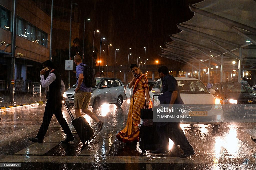 Air travellers cross a road at Delhi International Airport during heavy rain in New Delhi on June 28, 2016. / AFP / CHANDAN