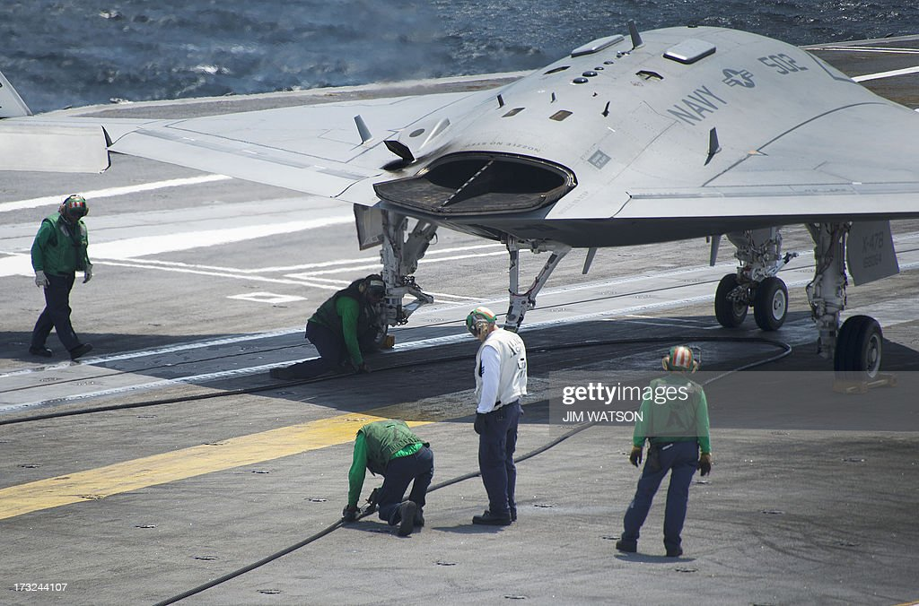 Air wing maintenance personnel check the arresting line after the X-47B Unmanned Combat Air System (UCAS) made the very first carrier landing aboard the USS George H.W. Bush while afloat in the Atlantic Ocean off the coast from Norfolk, VA, July 10, 2013.