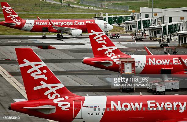 AirAsia Airbus A320 airplanes are parked on the tarmac at the lowcost carrier Kuala Lumpur International Airport 2 in Sepang on December 28 2014 An...