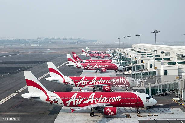 AirAsia Bhd aircraft stand next to boarding gates at Kuala Lumpur International Airport 2 in Sepang Malaysia on Tuesday June 24 2014 KLIA2 will...