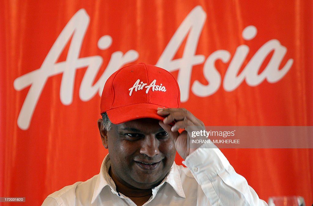 AirAsia's chief executive Tony Fernandes adjusts his cap at a press conference in Mumbai on July 1, 2013. Malaysia-based Asia's largest budget carrier AirAsia said that it has aggressive plans for its no-frills Indian airine joint venture later this year, with an aim to add ten aircraft each year. AirAsia, which won approval from India's foreign investment panel earlier this year to set up an airline in a joint venture with the giant Tata group and entrepreneur Arun Bhatia's Telstra Tradeplace. The company has already recruited 50 people, including pilots and engineers, he said, for the airline which plans to start operations later in 2013. AFP PHOTO/ INDRANIL MUKHERJEE