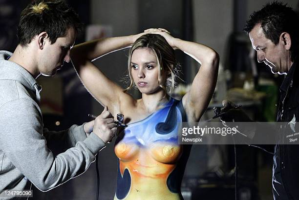 Airbrush artist Wayne Harrison painting a design on model Natalie Robinson with the help of his assistant Jeremy Richardson Television Sydney will be...