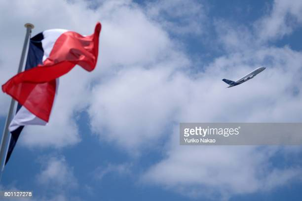 Airbus 380 flies past a fluttering French flag during an flying display over the Le Bourget Airport on the first public day of the 52nd International...