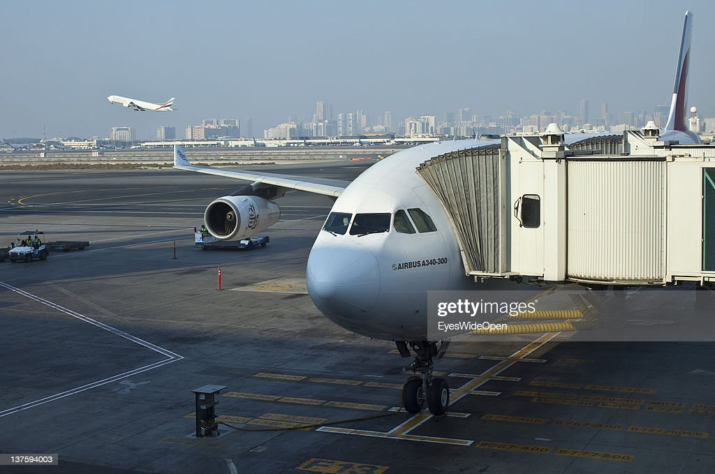 Airbus A340-300 at a gate with city view at Dubai Airport on December 25, 2011 in Dubai, United Arab Emirates