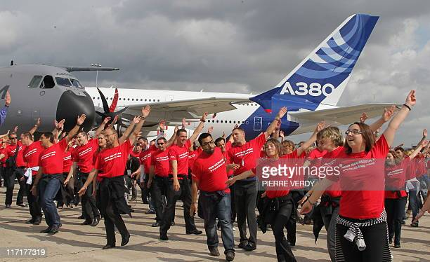 Airbus employees dance during a 'flash mob' on the tarmac on the first day of the public opening at the Paris International Air Show on June 24 2011...