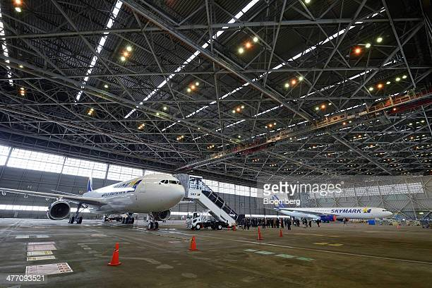 Airbus SAS A330 aircraft operated by Skymark Airlines Inc stand in a hangar during a media preview at Haneda Airport in Tokyo Japan on Friday March 7...