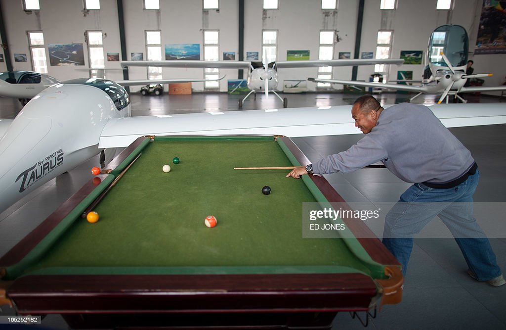 Aircraft broker and flight coach of the Beijing International United Flight Club, Zhang Changyi, plays pool before aircraft for sale at an 'aircraft supermarket' on the outskirts of Beijing on April 2, 2013. Selling gliders, helicopters, and powered light aircraft for prices up to 50 million yuan (around 8 million USD) the joint-venture trading company run by Beijing International United Flight Club is the first of its kind in the city and hopes to open the market to public buyers, although it has sold aircraft to club members for over 20 years. However, low-altitude airpace in China is still tighly controlled and despite hopes of liberalisation for private pilots, reports of secret or 'black' flights are not uncommon and are widely considered to be on the rise. AFP PHOTO / Ed Jones