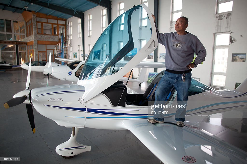 Aircraft broker and flight coach of the Beijing International United Flight Club, Zhang Changyi, stands on the wing of a 'Sting S4' light airplane at an 'aircraft supermarket' on the outskirts of Beijing on April 2, 2013. Selling gliders, helicopters, and powered light aircraft for prices up to 50 million yuan (around 8 million USD) the joint-venture trading company run by Beijing International United Flight Club is the first of its kind in the city and hopes to open the market to public buyers, although it has sold aircraft to club members for over 20 years. However, low-altitude airpace in China is still tighly controlled and despite hopes of liberalisation for private pilots, reports of secret or 'black' flights are not uncommon and are widely considered to be on the rise. AFP PHOTO / Ed Jones
