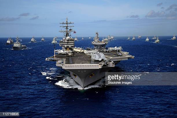 Aircraft carrier USS Ronald Reagan leads a mass formation of ships through the Pacific Ocean.