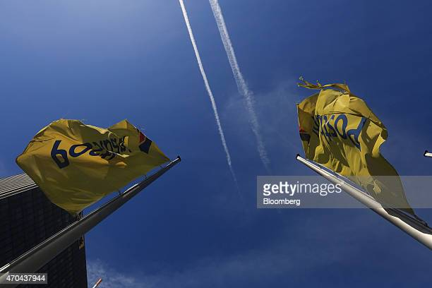 Aircraft contrails streak across the sky as banners fly outside the offices of Deutsche Postbank AG the consumer banking unit of Deutsche Bank AG in...