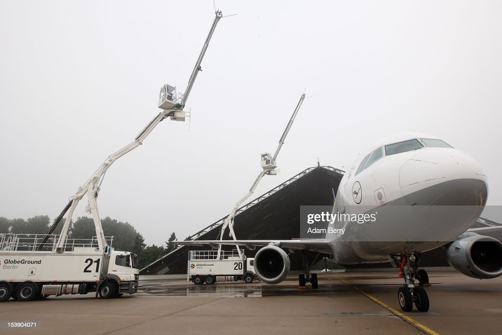 Aircraft deicers stand at full extension next to a Lufthansa Airbus A320 airplane on October 11 2012 in Berlin Germany The Berlin airports and...