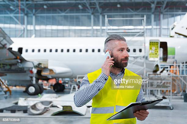 Aircraft engineer talking on mobile phone in a hangar