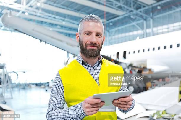 Aircraft engineer using a digital tablet in a hangar
