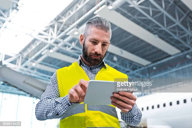 Aircraft engineer using a digital tablet in a hangar
