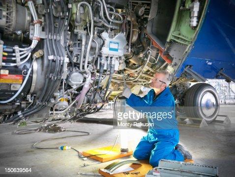 Aircraft engineer working on 737 engine in hangar