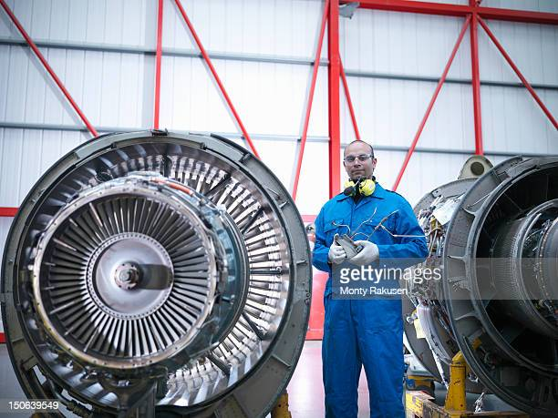 Aircraft engineer working on jet engine of jet airplane