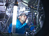 Aircraft engineer working on undercarriage area of 737 jet plane