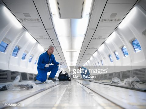 Aircraft engineers working on interior of 737 jet airplane