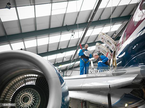 Aircraft engineers working on wing of 737 jet airplane in airport