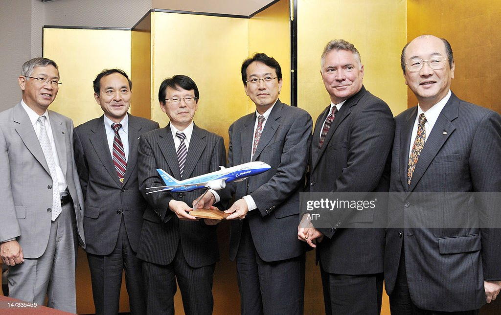 US aircraft giant Boeing vice president Matthew Ganz (2nd R) poses with Tokyo University professors Yoshiaki Nakano (3rd R) and Toshiyuki Obikawa (3rd L), and executives of Japanese aircraft manufacturers, Takashi Kobayashi (2nd L) from Mitsubishi Heavy Industries, Shigeru Murayama (L) from Kawasaki Heavy Industries and Hisashi Nagano from Fuji Heavy Industries (R) as they hold a scale model of the Boeing 787 jetliner at a press conference in Tokyo on June 28, 2012. The group said they formed a consortium to study the manufacturing of their aircraft. AFP PHOTO / Rie ISHII