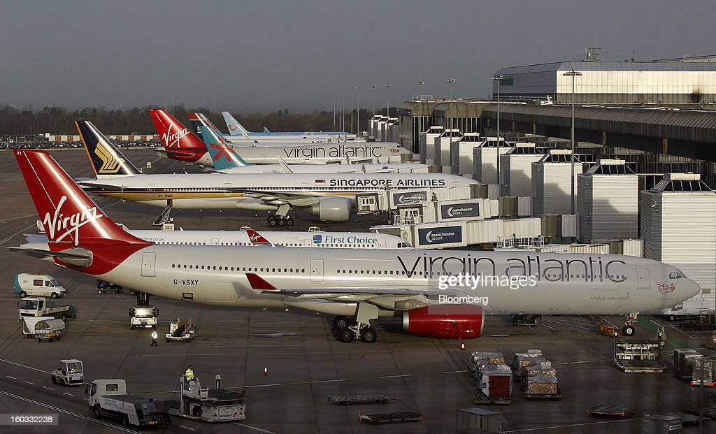Aircraft, including a Virgin Atlantic Airbus A330-300, front, sit parked at the gates of terminal two at Manchester airport in Manchester, U.K., on Tuesday, Jan. 29, 2013. Manchester Airports Group, owner of Britain's busiest airport outside London, is buying Stansted from Heathrow Airport Ltd., which is ceding 100 percent of Stansted to comply with regulatory requirements. Photographer: Paul Thomas/Bloomberg via Getty Images