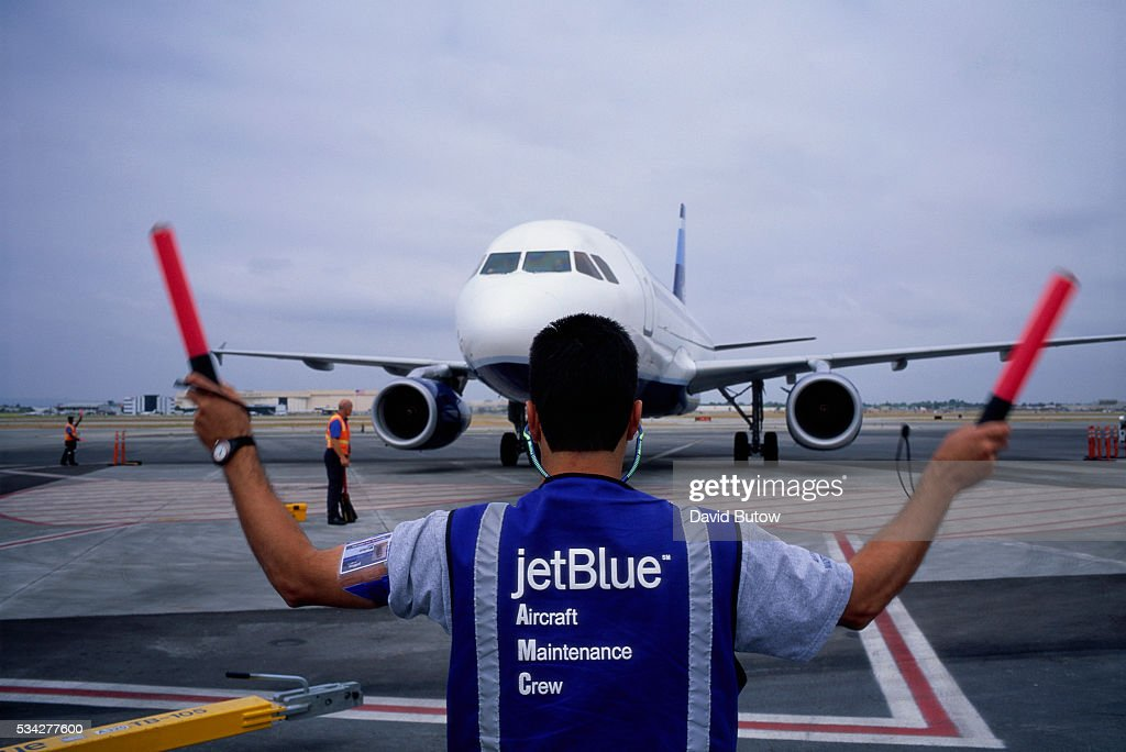 Aircraft maintenance crew personnel guide an arriving JetBlue flight on the tarmac at Long Beach Airport
