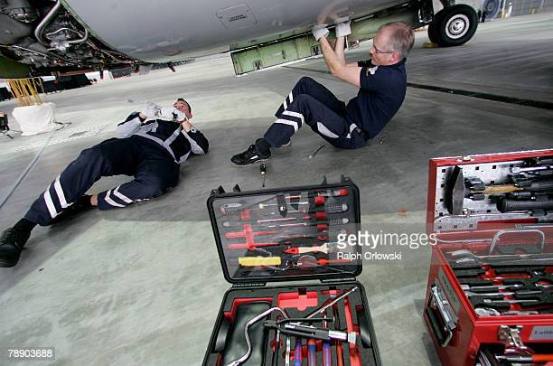 Aircraft mechanics check a jet engine of an Airbus 320 at the Lufthansa A380 hangar at Frankfurt airport January 11 2008 in Frankfurt Germany...