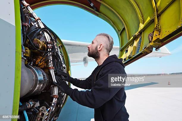 Aircraft mechnic examining aircraft engine