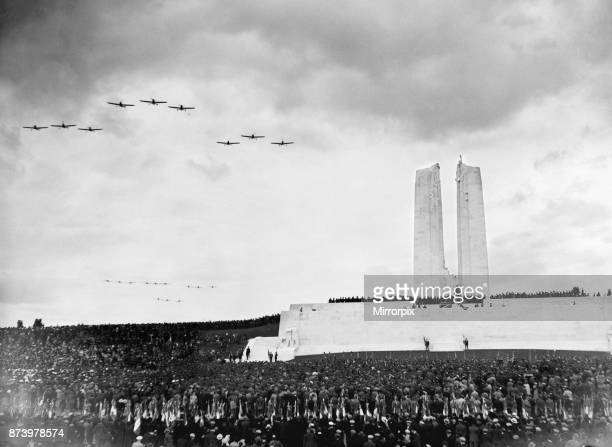 Aircraft of the Royal Air Force and French Air Force dip their wings in salute as they fly over the Canadian War Memorial at Vimy Ridge during the...