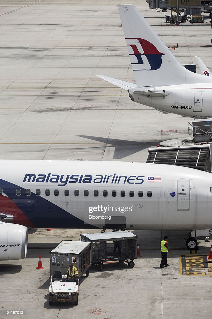 Aircraft operated by Malaysian Airline System Bhd. (MAS) stand on the tarmac at Kuala Lumpur International Airport (KLIA) in Sepang, Malaysia, on Tuesday, Aug. 26, 2014. Malaysia Airlines are scheduled to release second quarter earnings Aug. 27 as the airline considers job cuts, a review of aircraft orders and replacing its chief executive officer after the national carrier suffered two disasters this year, people familiar with the plan said. Photographer: Charles Pertwee/Bloomberg via Getty Images