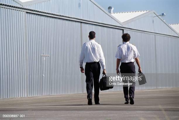 Aircraft pilots walking near hangars, rear view