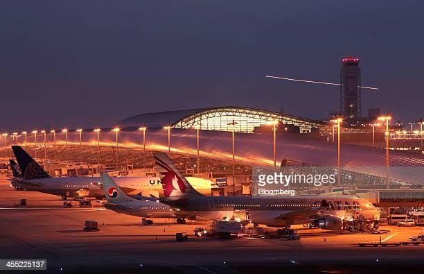 Aircraft sit on the tarmac at Kansai International Airport operated by New Kansai International Airport Co at night in Izumisano City Osaka Japan on...